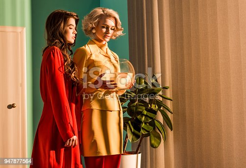 109350576 istock photo retro styled girls in colorful dresses holding aquarium with gold fish at home 947877564