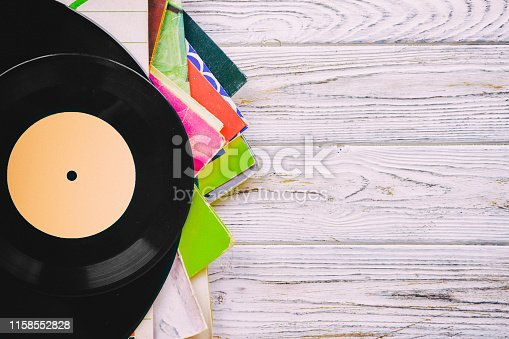 istock Retro styled image of a collection of old vinyl record lp's with sleeves on a wooden background with Copy space top view toned 1158552828