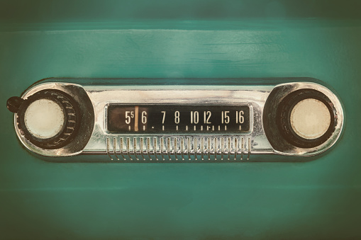 Retro styled image of an old car radio inside a green classic car