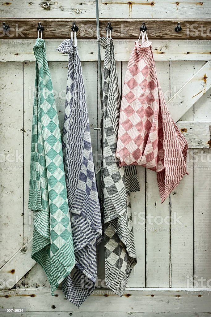 Retro styled image of hanging dish cloths on an old wooden door