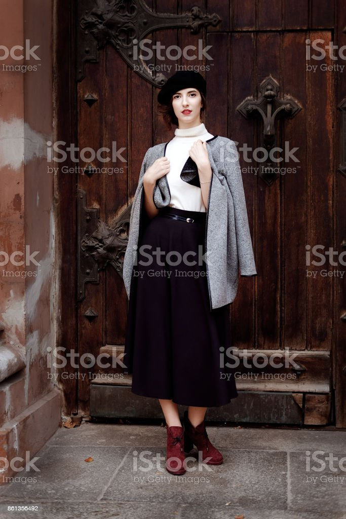 Retro styled portrait. Teacher woman in old fashioned classic outfit at the entrance to the gothic castle. stock photo