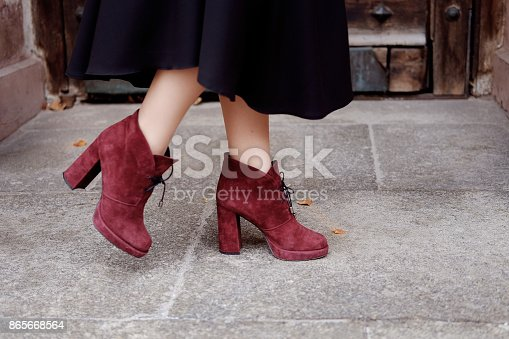 Retro styled portrait. Teacher woman in old fashioned classic outfit wearing burgundy suede boots on heels at the entrance.