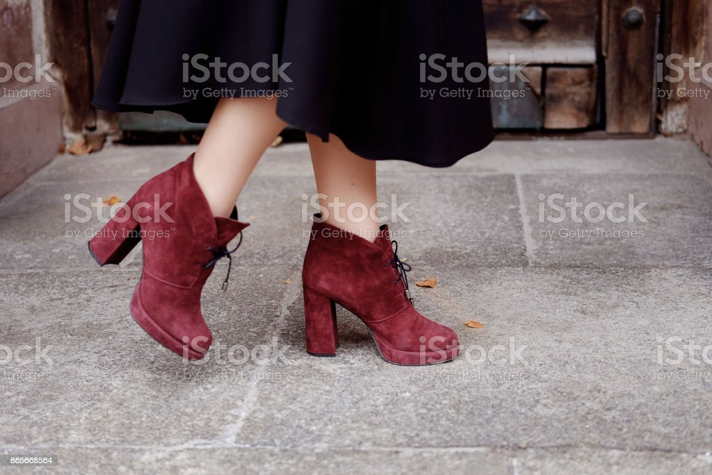 Retro styled portrait. Teacher woman in old fashioned classic outfit wearing burgundy suede boots on heels at the entrance. stock photo