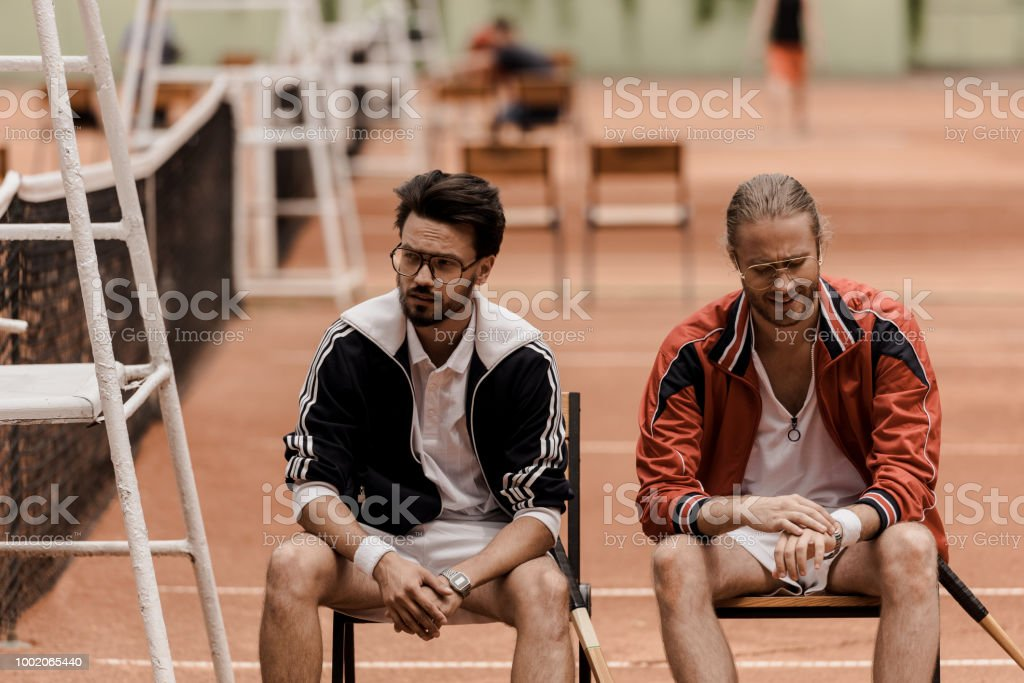Retro Styled Tennis Players Sitting On Chairs At Tennis Court Royalty Free  Stock Photo