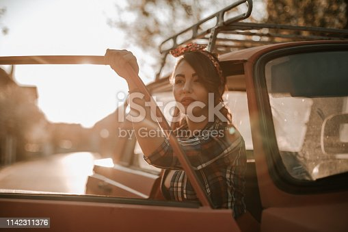Retro styled woman in vintage car on a sunny summer day