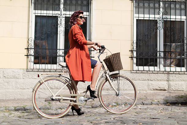 retro styled woman riding a bike - 1940s style stock photos and pictures