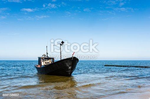 932662672istockphoto Retro stylized, fishing boat on the coast. 655158652