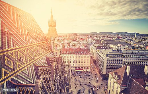 Retro stylized picture of Vienna at sunset, view from the north tower of St. Stephen's Cathedral, Austria.