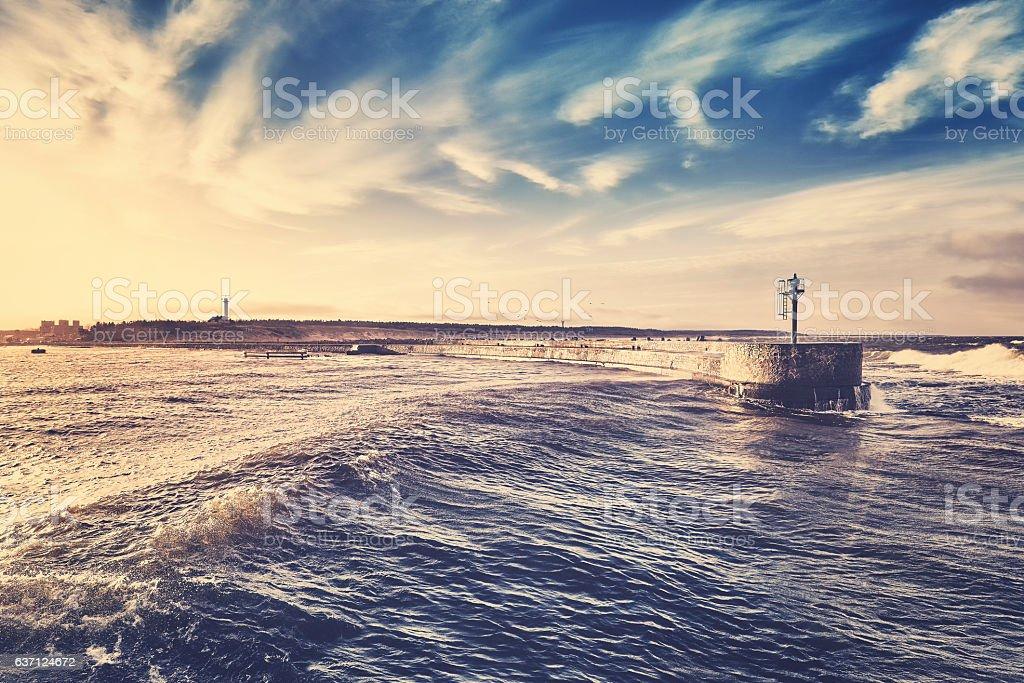 Retro stylized sunset over port entrance. stock photo