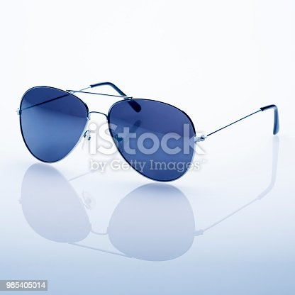 This is a photo of sunglasses isolated on a white background with a reflection below. They look a bit like policeman glasses.