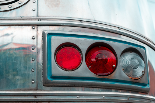 Retro tail lights on silver vehicle with rivets and chrome