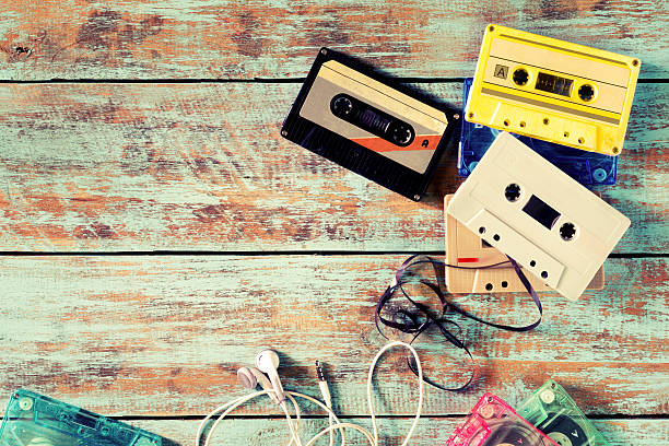 Retro tape cassette Top view (above) shot of retro tape cassette with earphone on wood table - vintage color effect styles. audio cassette stock pictures, royalty-free photos & images