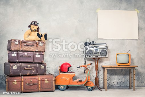 istock Retro Teddy Bear toy in aviator's hat, aged travel valises, children's pedal scooter, helmet, cassette boombox with headphones, TV, paper poster blank on concrete wall. Vintage style filtered photo 1254368866