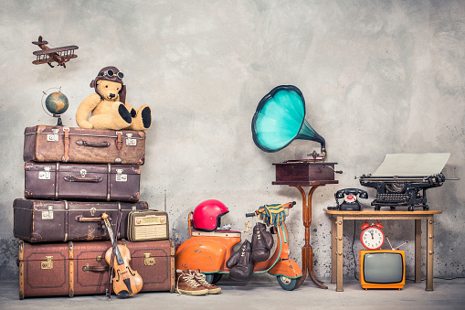 istock Retro Teddy Bear toy in aviator's hat, wooden plane, aged classic travel valises, globe, children pedal scooter, phonograph, typewriter, clock, TV, radio, old telephone. Vintage style filtered photo 1048867404