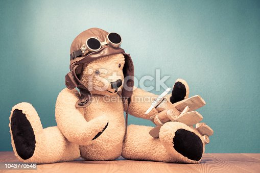 istock Retro Teddy Bear toy in leather pilot's hat and vintage goggles sitting on the floor and playing with handmade wooden plane front mint green wall background. Old style filtered photo 1043770546