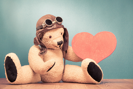 Retro Teddy Bear Toy In Leather Pilots Hat And Vintage Goggles Sitting On  The Floor With