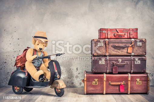 Retro Teddy Bear toy in tourist hat sitting on old rusty children's pedal scooter from 60s, leather backpack and outdated trunks luggage, antique valises. Travel concept. Vintage style filtered photo