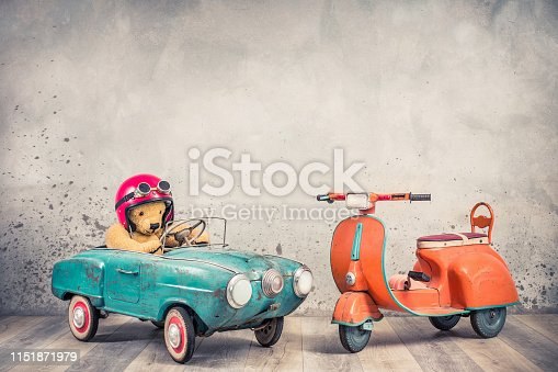 istock Retro Teddy Bear toy racer in old helmet hat with goggles driving antique rusty mint blue pedal car from 60s and orange kids scooter trike front concrete wall background . Vintage style filtered photo 1151871979