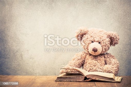 istock Retro Teddy Bear toy sitting at the old wooden desk with old book front concrete wall background. Vintage instagram style filtered photo 1065770388