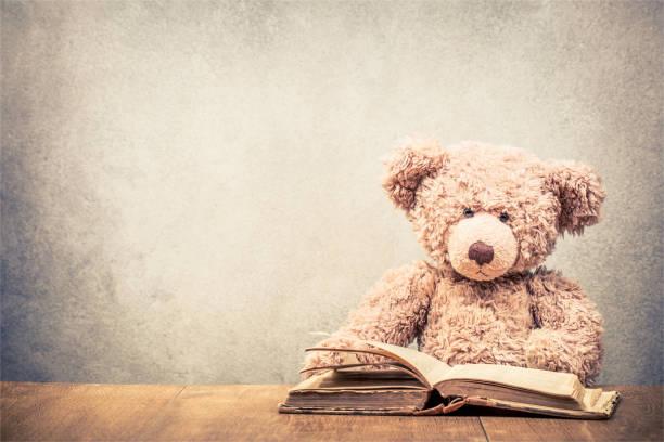 retro-teddybär spielzeug mit alten buch konkrete vorderwand hintergrund am alten hölzernen schreibtisch sitzen. vintage instagram stil gefilterten foto - bibliothekschilder stock-fotos und bilder