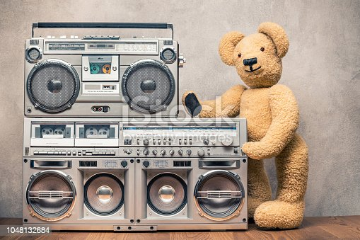 1043737676 istock photo Retro Teddy Bear toy standing near boombox cassette ghetto blasters radio recorders from 80s front concrete wall background. Vintage old style filtered photo 1048132684