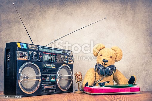1043737676 istock photo Retro Teddy Bear toy with headphones at the DJ turnable mixing console, classic mic, old cassette ghetto blaster radio recorder from 80s front concrete wall background. Vintage style filtered photo 1051139834
