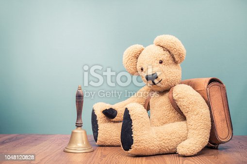 istock Retro Teddy Bear toy with leather school bag and old bronze bell front mint green wall background. Vintage style filtered photo 1048120828