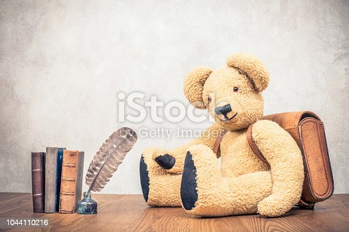 istock Retro Teddy Bear toy with leather school bag near quill pen in the inkwell and old books front concrete wall background. Vintage style filtered photo 1044110216