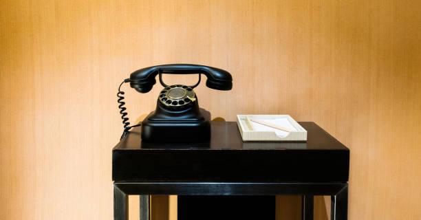 retro telefon auf einem holztisch - nostalgie telefon stock-fotos und bilder