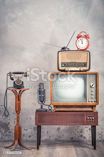 1056306726istockphoto Retro television from 50s, old microphone, radio receiver, orange alarm clock on wooden TV stand and outdated telephone front aged textured concrete wall background. Vintage style filtered photo 1153532328