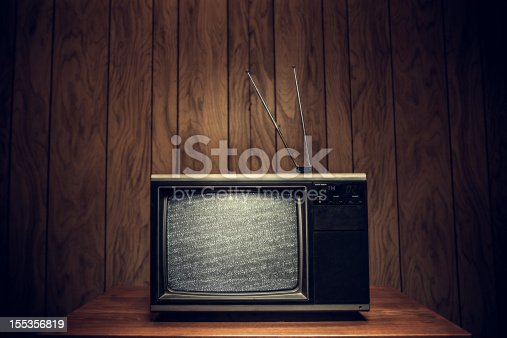 Static plays on the screen of an old 1980's TV complete with signal antennae, sitting on a table in a domestic room with wood paneling on the walls.  Horizontal with copy space.