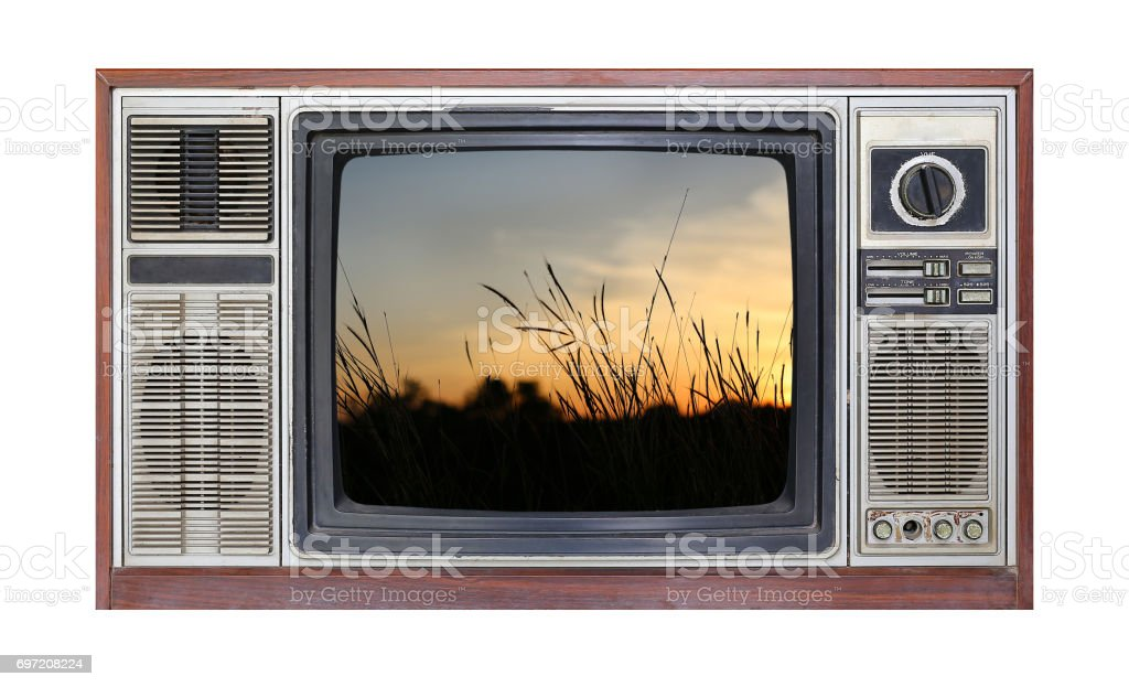 Retro television on white background with image of dried grass at sunset on screen. stock photo