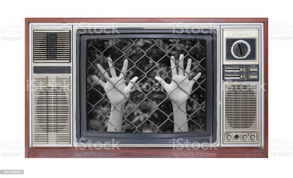 Retro television on white background with image of Hands touching a metal fence on screen. stock photo