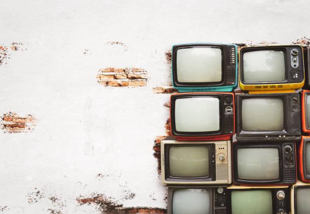 Retro televisions pile on floor stock photo