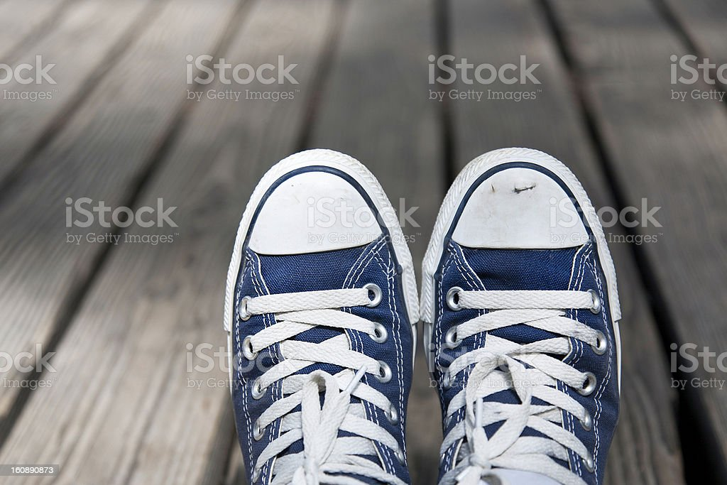 Retro tennis shoes over wooden floor royalty-free stock photo