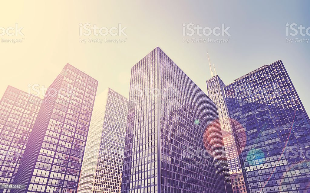 Retro toned photo of Chicago city skyscrapers against sun. stock photo