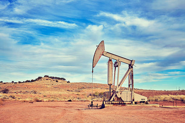 Retro toned picture of an old oil pump. stock photo