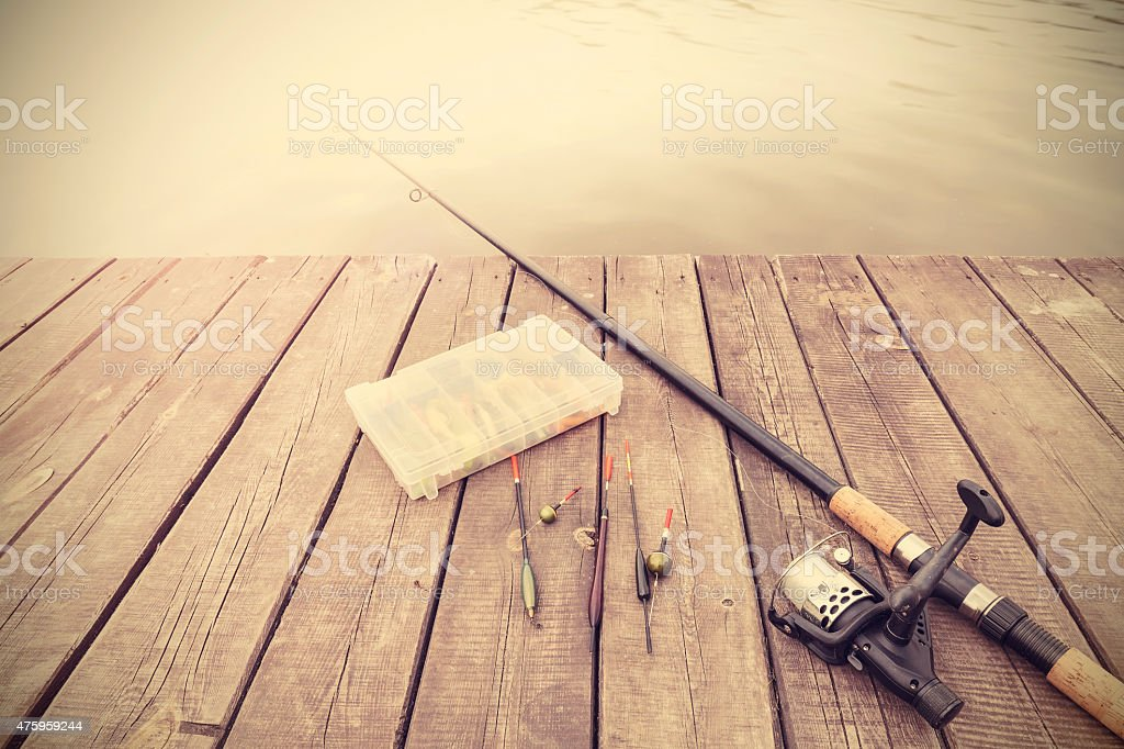 Retro toned picture of fishing equipment on wooden pier.