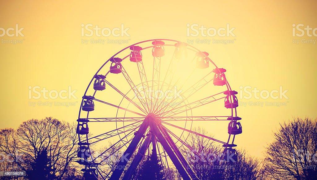 Retro toned silhouette of ferris wheel at sunset. stock photo
