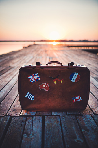 Retro tourist's suitcase with flag stickers on lake pier on sunset