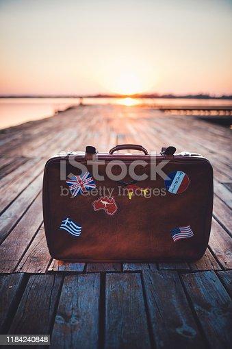 istock Retro tourist's suitcase with flag stickers 1184240848