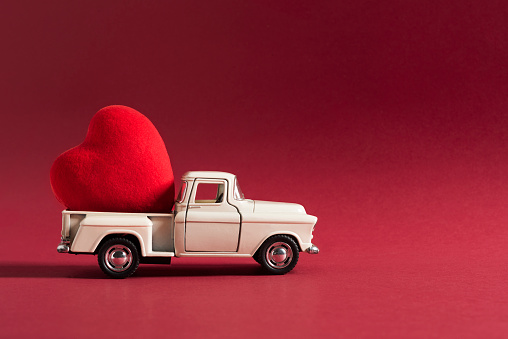 retro toy car delivering craft heart for Valentine's day on red background. Valentines Day concept.