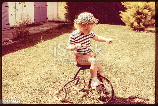 Grainy retro image of a cute girl riding a tricycle. original photographic slide.
