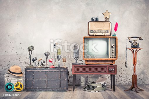 1056306726istockphoto Retro TV, old studio microphones, outdated broadcast radio, journalist's reel tape recorder, aged telephone, film camera, golden award star, quill, typewriter. Journalism concept. Vintage style photo 1153730522