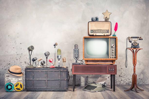 Retro TV, alte Studiomikrofone, veraltetes Rundfunkradio, Journalisten-Rekorder, gealtertes Telefon, Filmkamera, goldener Award-Star, Quill, Schreibmaschine. Journalismus-Konzept. Vintage-Stil Foto – Foto