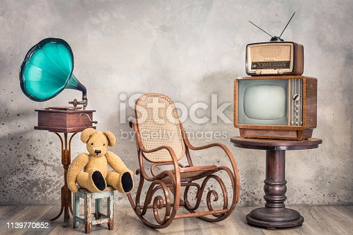 Retro TV receiver and old broadcast radio from circa 50s on wooden table, outdated gramophone, Teddy Bear toy, aged rocking chair front textured concrete wall background. Vintage style filtered photo