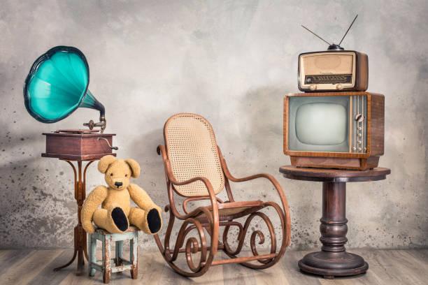 Retro-Fernsehempfänger und altes Rundfunkradio aus ca. 50er Jahren auf Holztisch, veraltetes Grammophon, Teddybären-Spielzeug, gealterter Schaukelstuhl mit getexiertem Betonwandhintergrund. Vintage-Stil gefiltert Foto – Foto