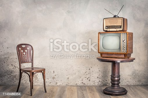 istock Retro TV receiver and outdated broadcast radio from circa 50s on wooden table and old chair front textured concrete wall background. Vintage style filtered photo 1143486354