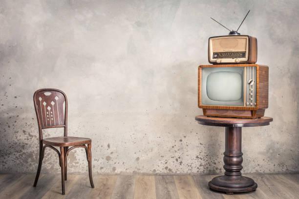 Retro-Fernsehempfänger und veraltetes Rundfunkradio aus ca. 50er Jahren auf Holztisch und alter Stuhlfront strukturierter Betonwandhintergrund. Vintage-Stil gefiltert Foto – Foto