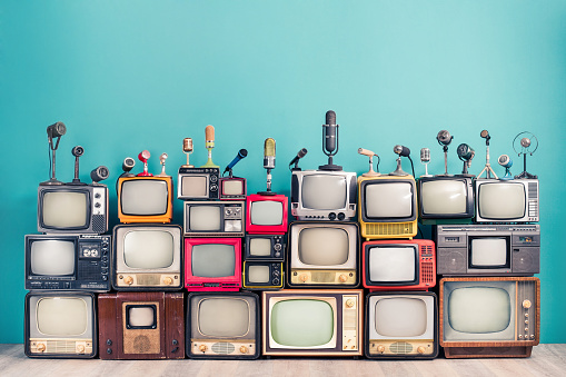 Retro TV receivers set from circa 60s, 70s and 80s of XX century, old classic microphones for press conference front mint blue wall background. Broadcasting, news concept. Vintage style filtered photo